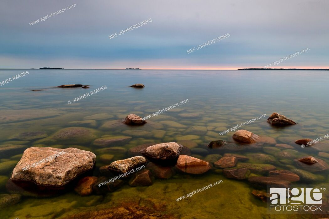 Stock Photo: Rock formations by sea at dawn.