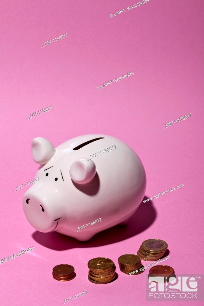 Stock Photo: A piggy bank and stacks of European Union coins.