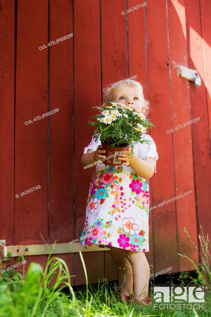 Stock Photo: Girl holding potted plant outdoors.