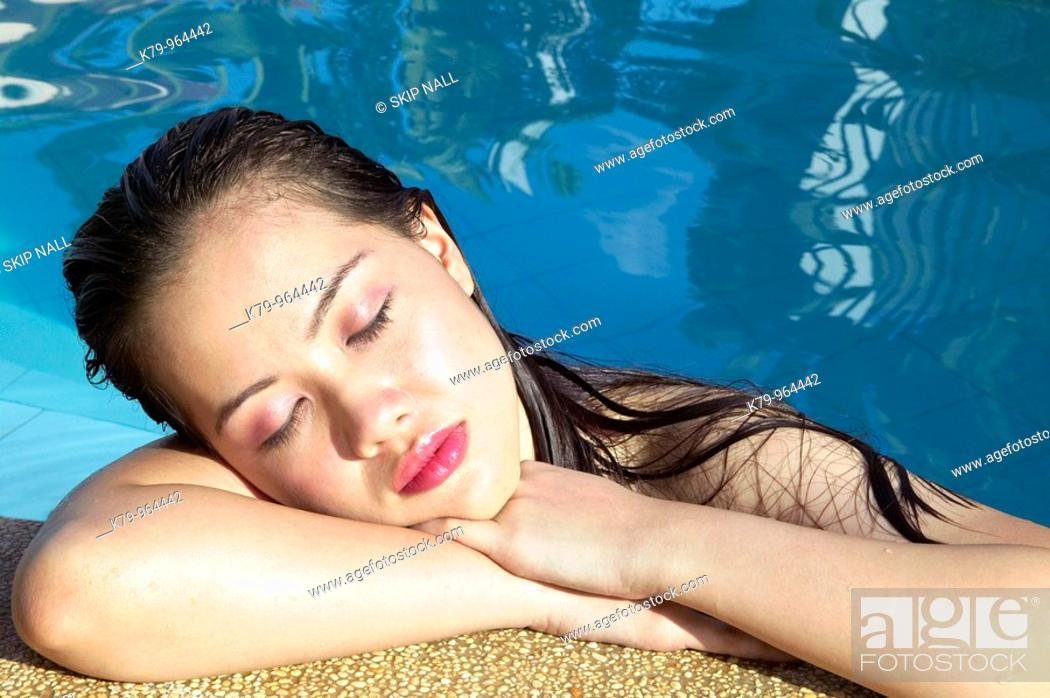 Stock Photo: Pretty Asian young woman relaxing in swimming pool with eyes closed.