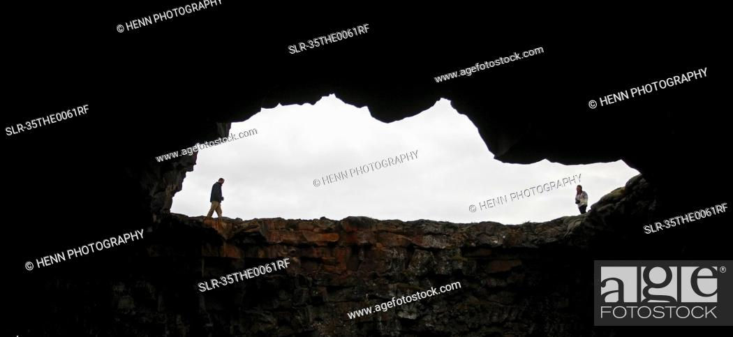 Stock Photo: People walking around mouth of cave.