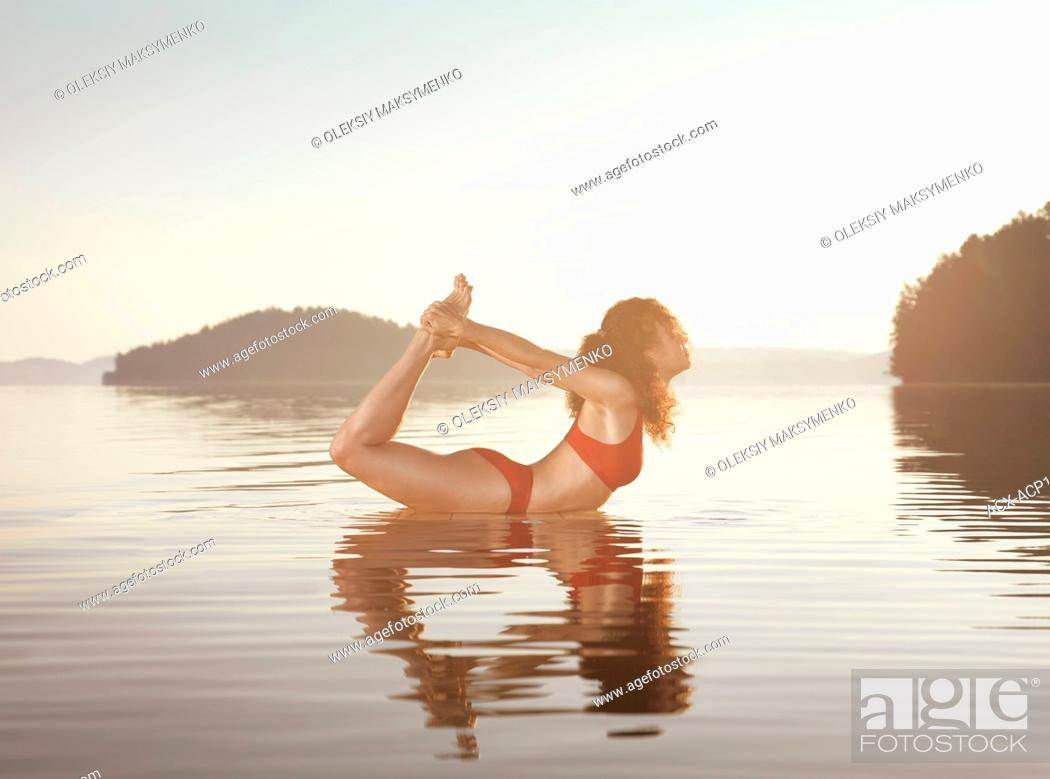Stock Photo: Young woman practicing yoga on a floating platform in water on the lake during misty sunrise in the morning. Yoga Bow posture, Dhanurasana.