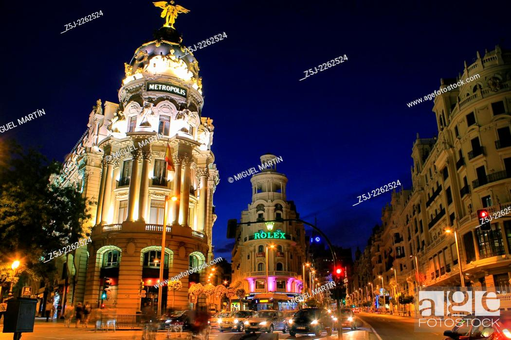 Stock Photo: Twilight scene at street junction between Alcalá street and Gran Vía, one of the busiest in Madrid, framed by some notable landmarks like Metrópolis Building.
