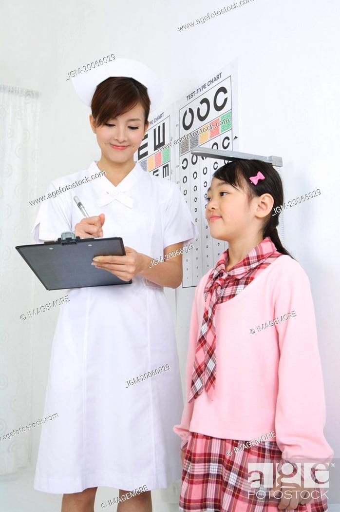 Stock Photo: Young nurse writing on clipboard for little girl's height.