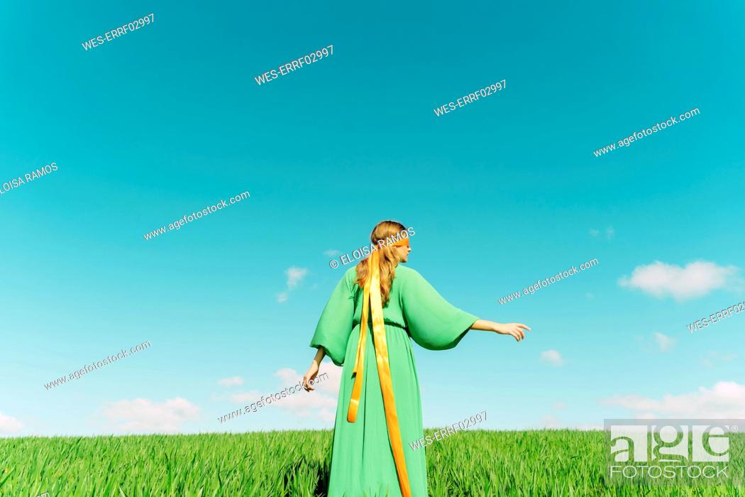 Stock Photo: Rear view of young woman wearing a green dress standing in a field with a ribbon around her head.