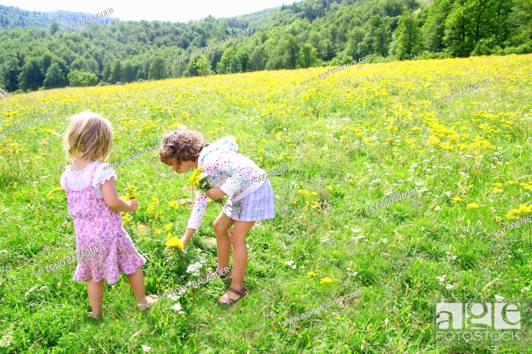 Stock Photo: sister girls in meadow playing with spring flowers outdoor.