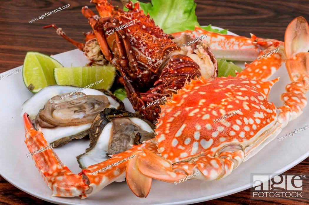 Stock Photo: Spiny lobster, crab and oyster on the bowl with lime.