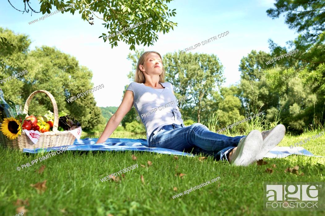 Stock Photo: Germany, Cologne, Young woman relaxing at picnic.