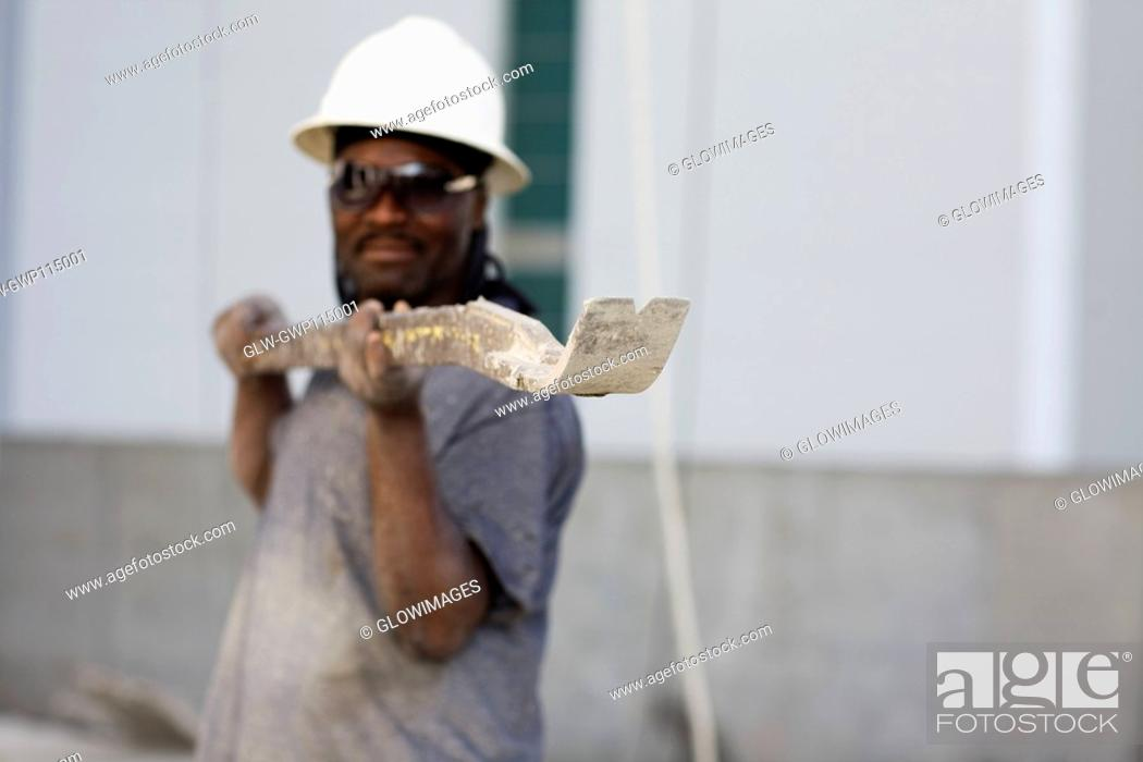 Stock Photo: Male construction worker holding a work tool.