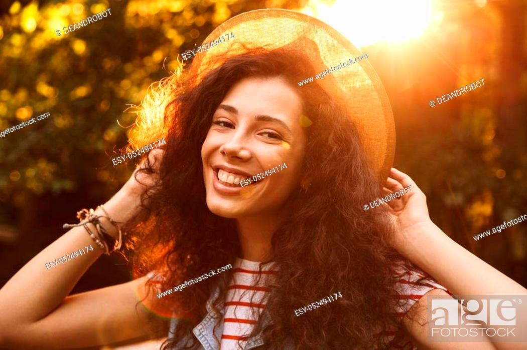 Stock Photo: Photo closeup of brunette smiling girl 18-20 wearing straw hat looking at you, while walking through park in sunny day with trees background.