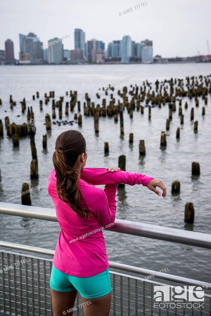 Stock Photo: Woman stretching on bridge.