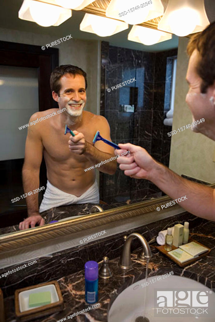 Stock Photo: Reflection of a young man holding a razor in a mirror.