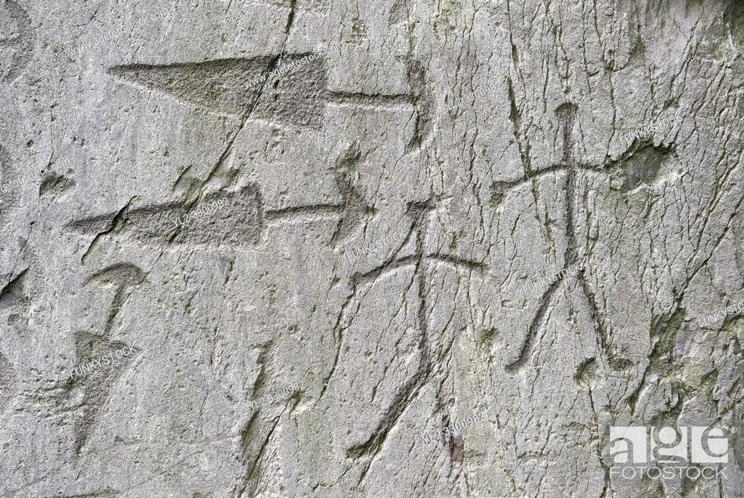 Stock Photo: Prehistoric petroglyphs, rock carvings, detail of of trangular daggers with semi circular pomels and schematic depictions of human figures in an ancient.