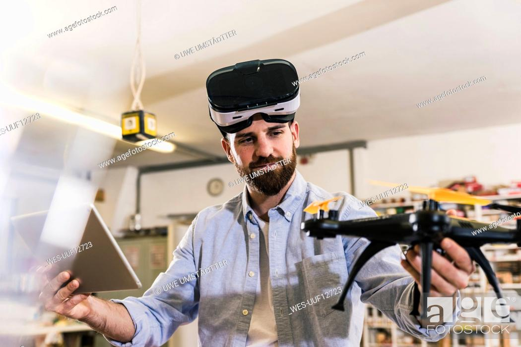 Stock Photo: Man wearing VR glasses holding drone and tablet.