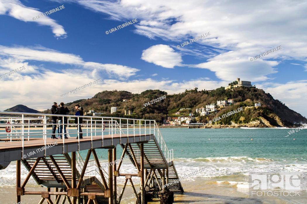 Stock Photo: People gather on the bridge to admire the beautiful view of Santa Clara Island in the city of San Sebastian.