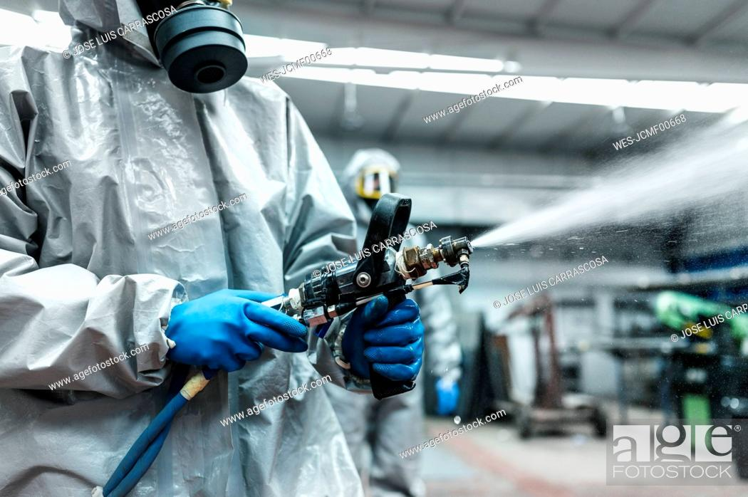 Imagen: Midsection of disinfection worker spraying decontamination chemical from hose in warehouse.