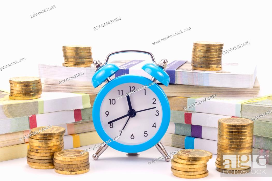Stock Photo: Hours stand before a pack of notes, around there are stacks of coins.