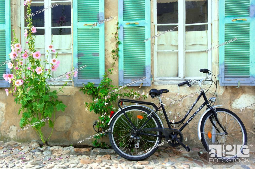 Stock Photo: Bicycle in front of a House surrounded by flowers and Hollyhock Alcea Rosa, Saint Martin en Re, Ile de Re, Charentes Maritime department, France, Europe.