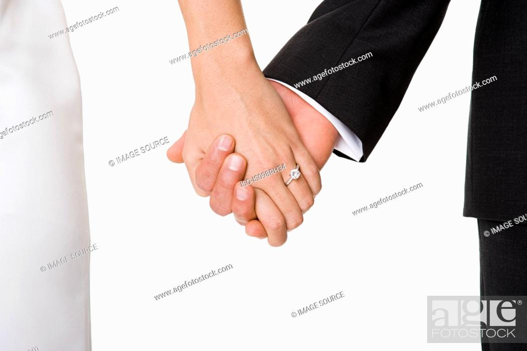 Stock Photo: Newlywed couple holding hands.