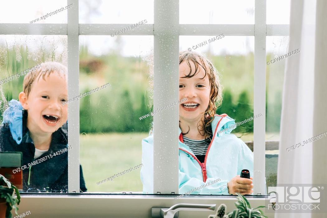 Stock Photo: brother and sister spraying the windows with water whilst playing.