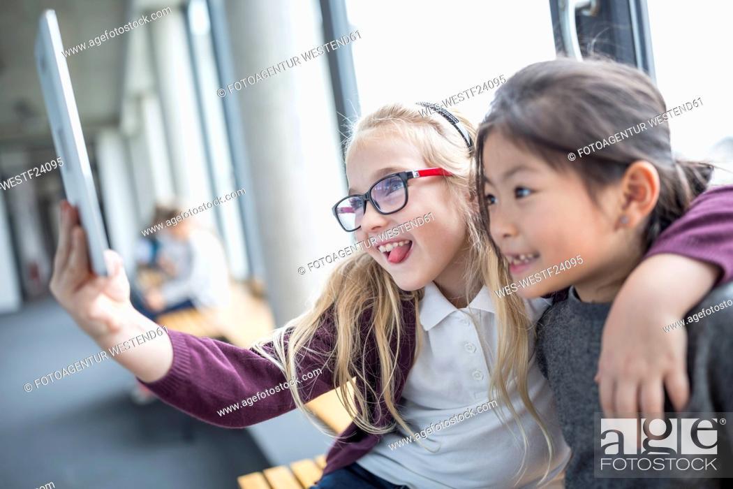 Photo de stock: Happy schoolgirls taking a selfie with tablet on school corridor.