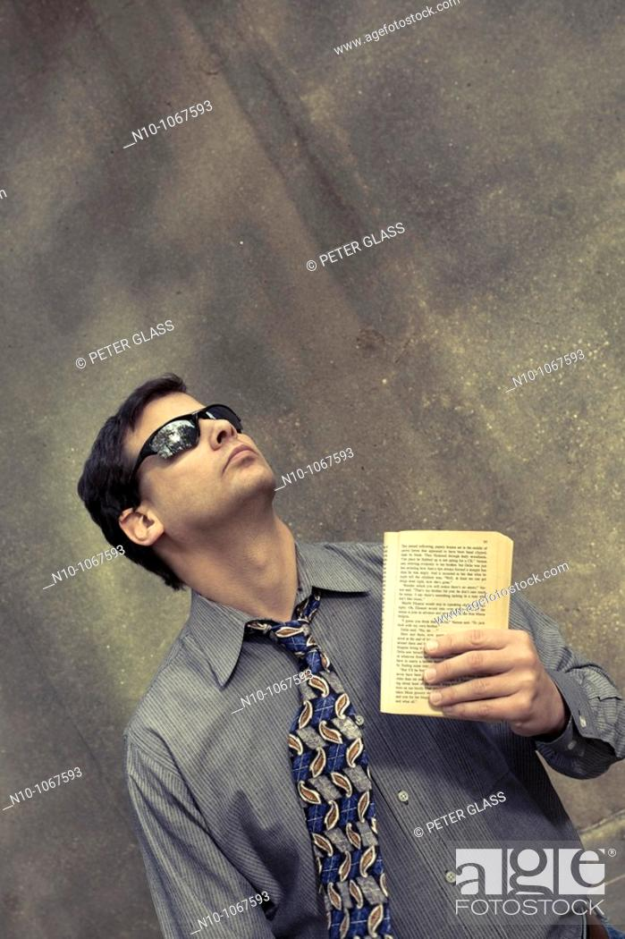 Stock Photo: Young man outside, holding a book.
