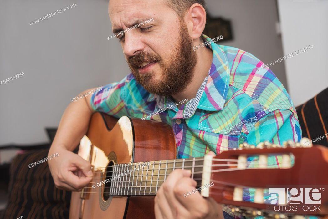 Imagen: Young man musician playing acoustic guitar.