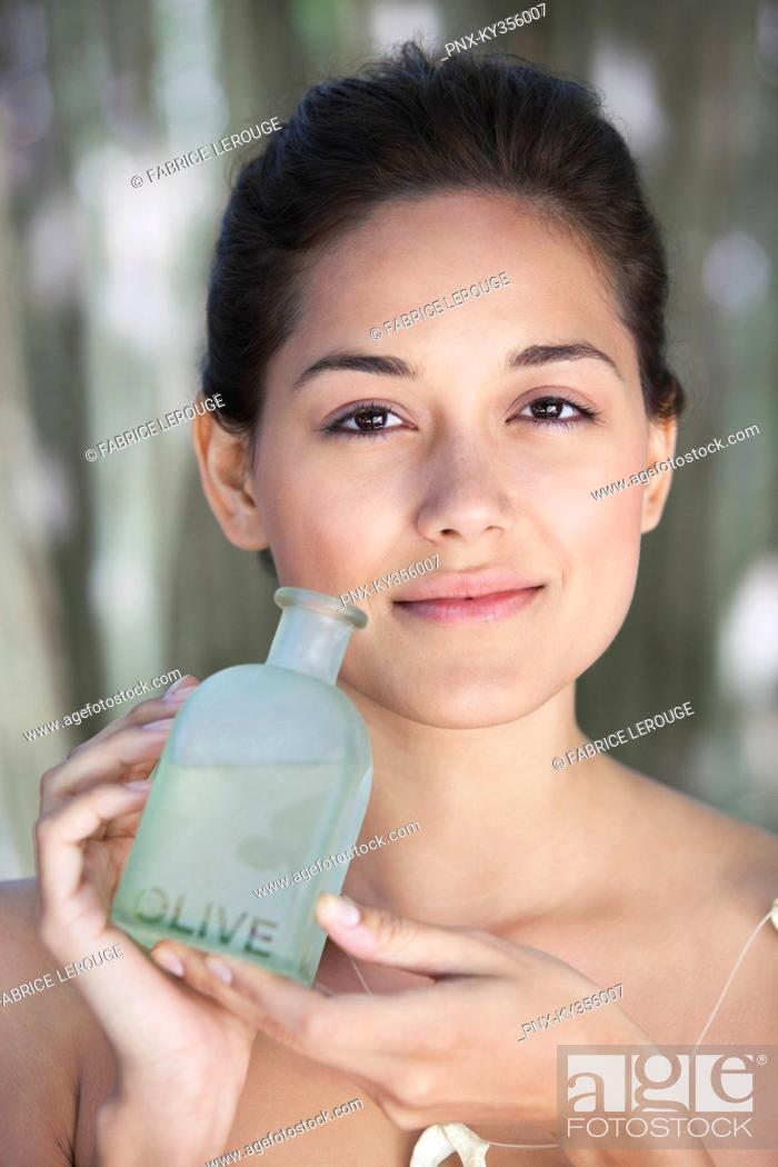 Stock Photo: Portrait of a beautiful young woman holding bottle of olive oil.