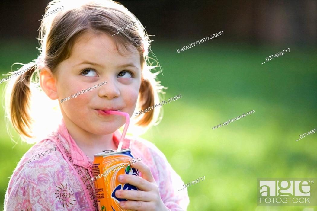 Stock Photo: Little girl drinking soda in the garden.