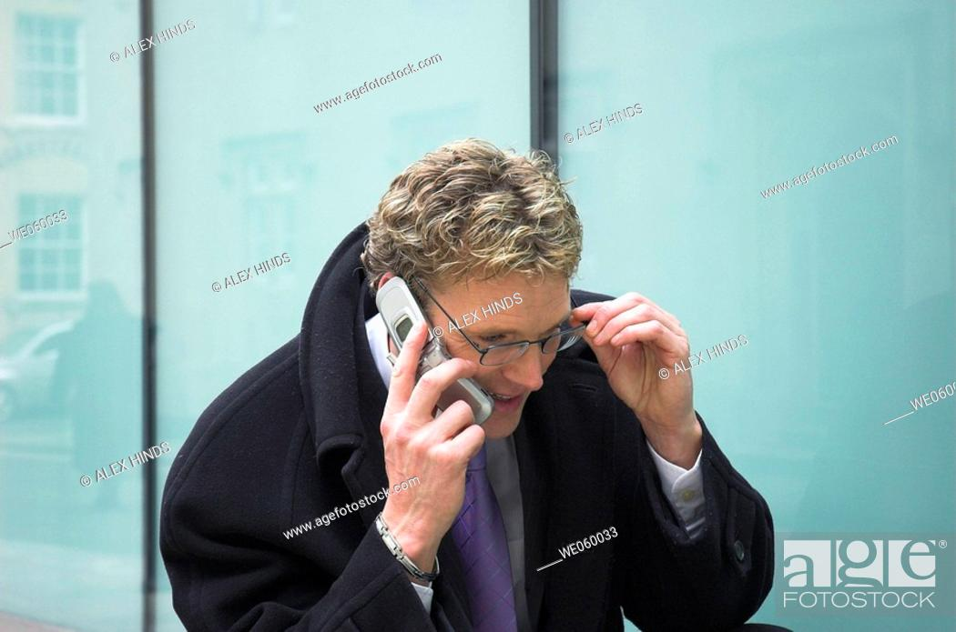 Stock Photo: Young businessman outside talking on a mobile phone.