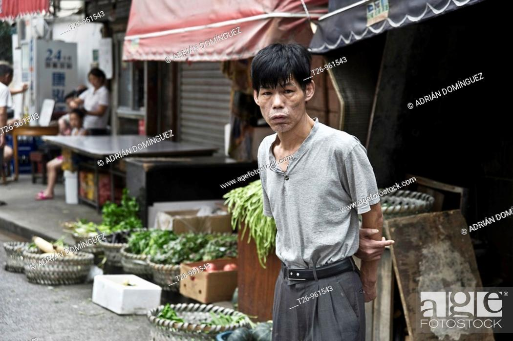 Stock Photo: A man looks at a camera in the Shanghai market, China.