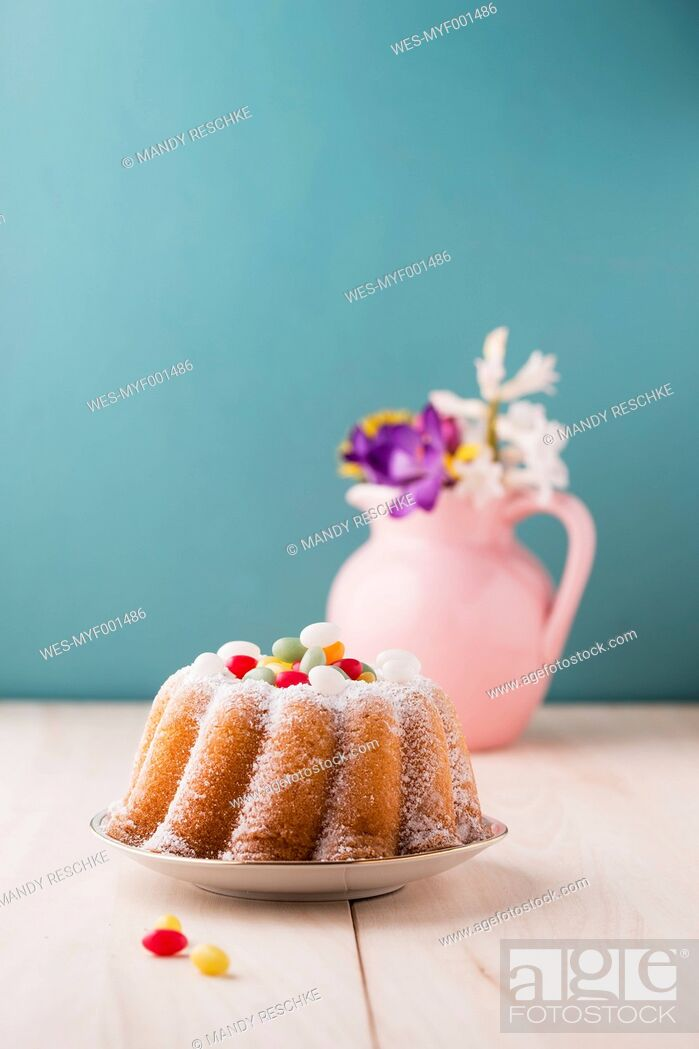 Stock Photo: Ring cake with Easter eggs and bunch of flowers in the background.