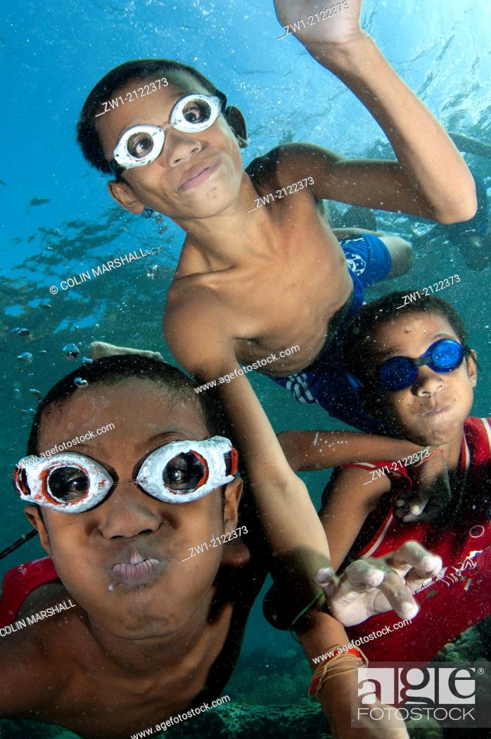 Imagen: Trio of boys with goggles playing in the water at Pura Island near Alor in eastern Indonesia.
