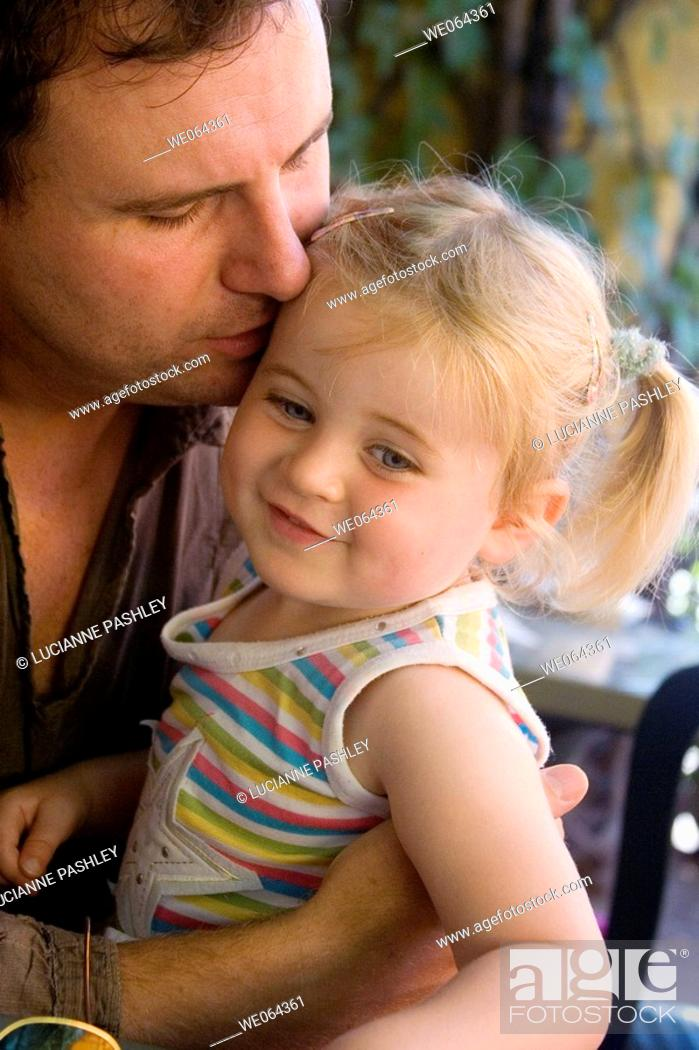 Stock Photo: father kissing his 3 year old daughter on the cheek.