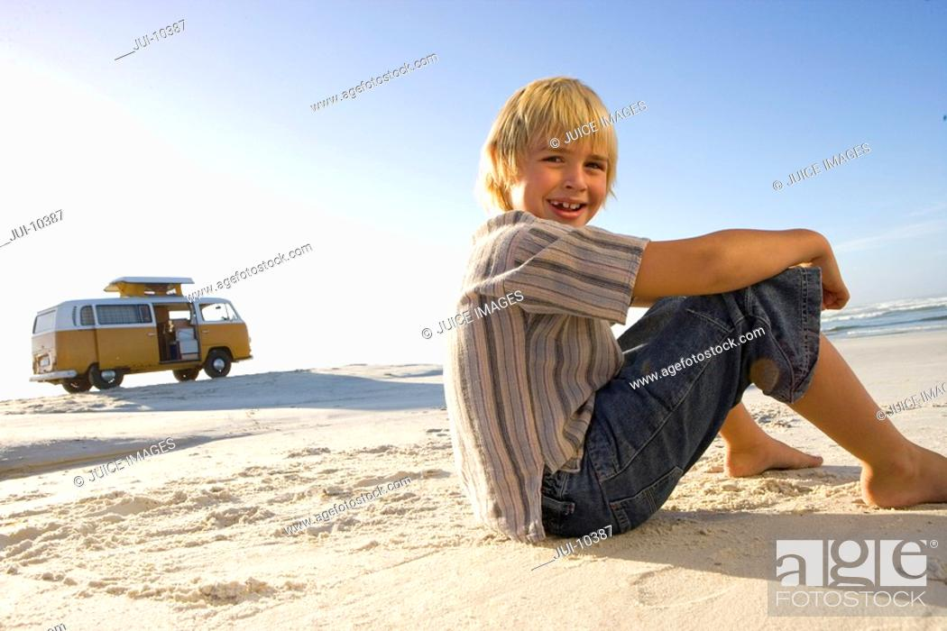 Stock Photo: Boy 6-8 sitting on beach, camper van in background, smiling, portrait, low angle view.