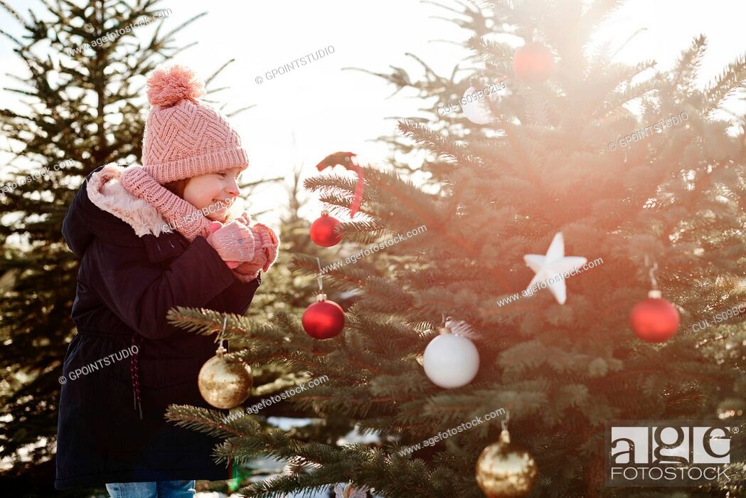 Stock Photo: Girl looking at baubles on forest christmas tree.