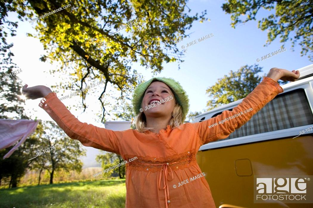 Stock Photo: Girl 9-11 with arms raised by camper van in field, smiling, low angle view.