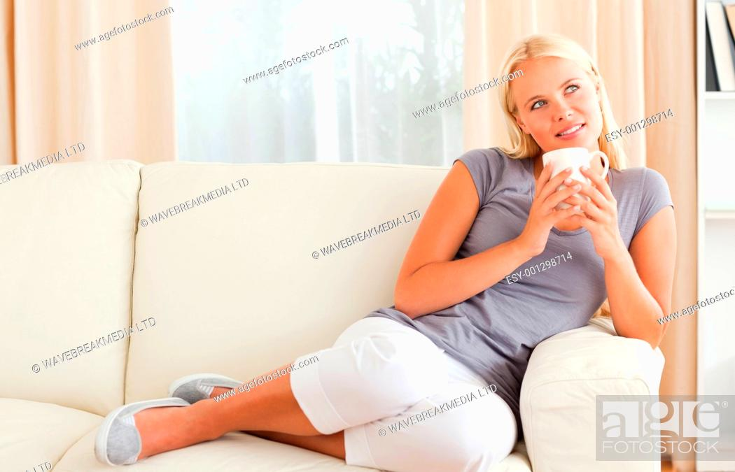 Stock Photo: Woman holding a cup of coffee while looking away from the camera.