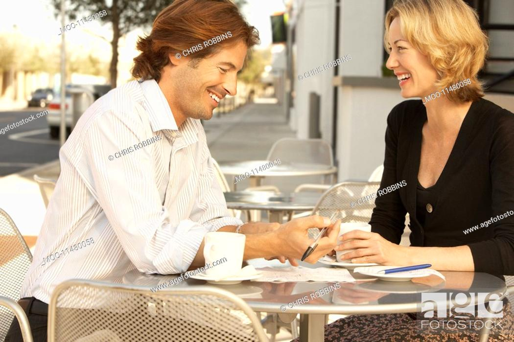 Stock Photo: Couple smiling at outdoor cafe.