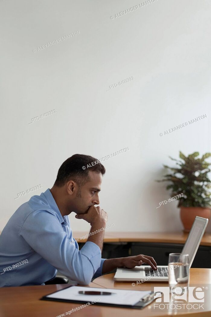 Stock Photo: Singapore, Businessman using laptop in office.