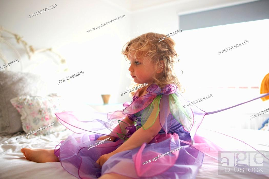 Stock Photo: Young girl dressed in fairy costume, sitting on bed.