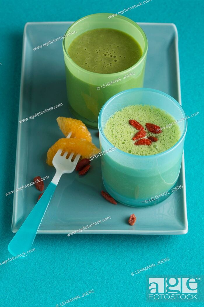 Stock Photo: A green smoothie made with mandarin, and a banana and pineapple smoothie with goji berries.