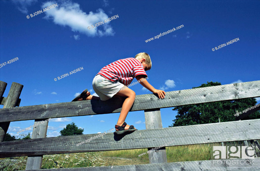 Stock Photo: Boy climbing over a fence.