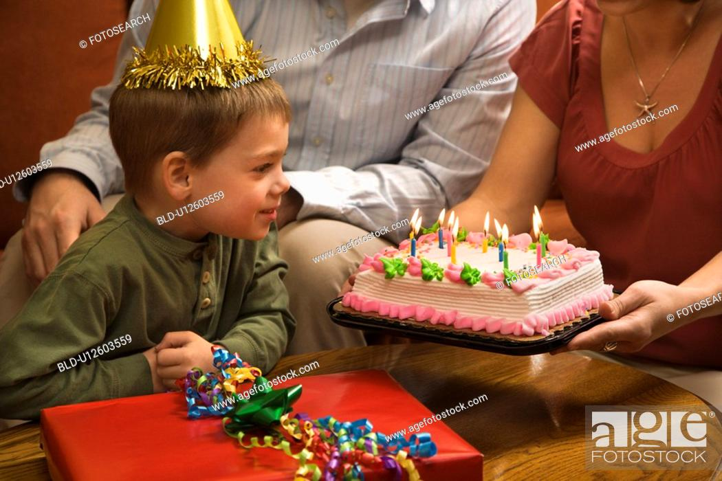 Stock Photo: Boy in party hat with Birthday cake and family.