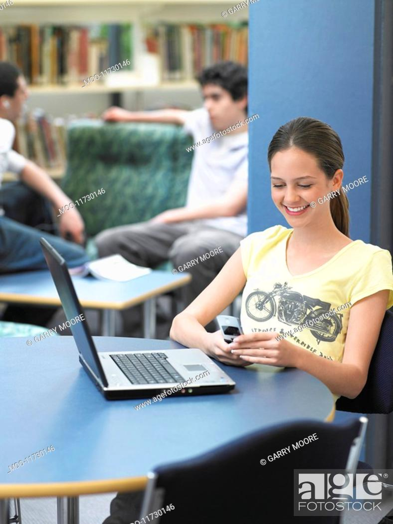 Stock Photo: Teenage girl texting sitting in library.