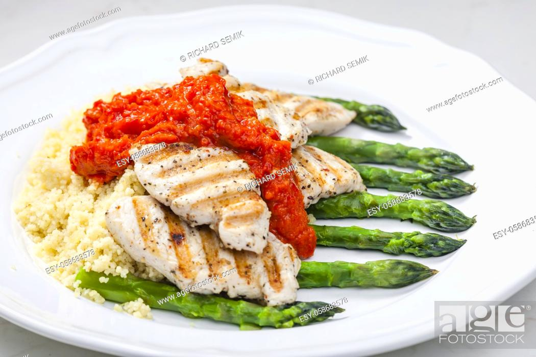 Imagen: grilled poultry meat with baked red pepper sauce and green asparagus.