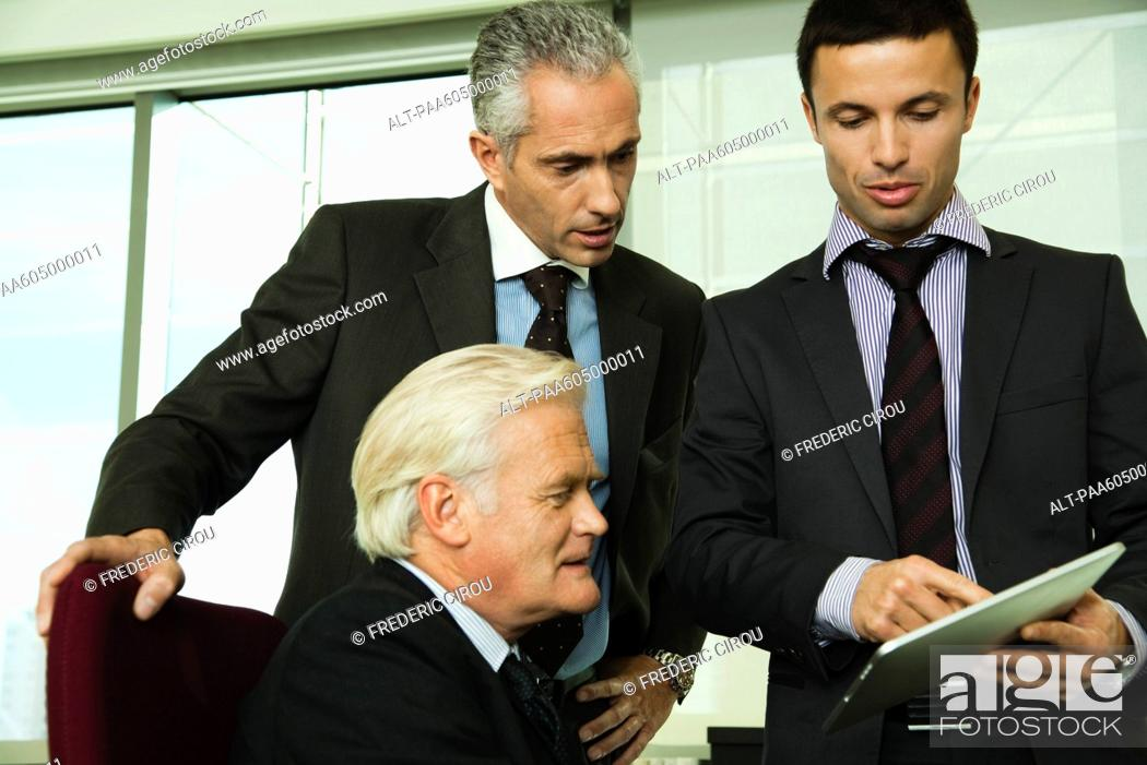 Stock Photo: Young businessman showing mature executives how to use digital tablet.