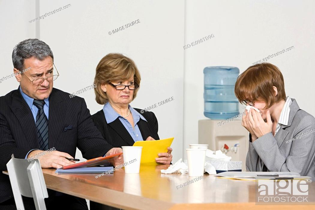 Stock Photo: Businesswoman blowing nose in office.