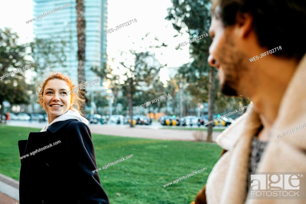 Stock Photo: Smiling young woman turning round looking at boyfriend.