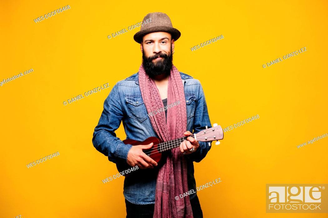 Imagen: Portrait of a bearded young man in studio holding ukulele.